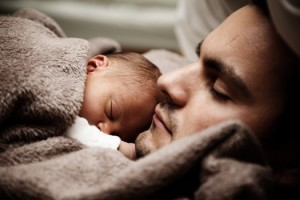 Father sleeping with newborn baby.